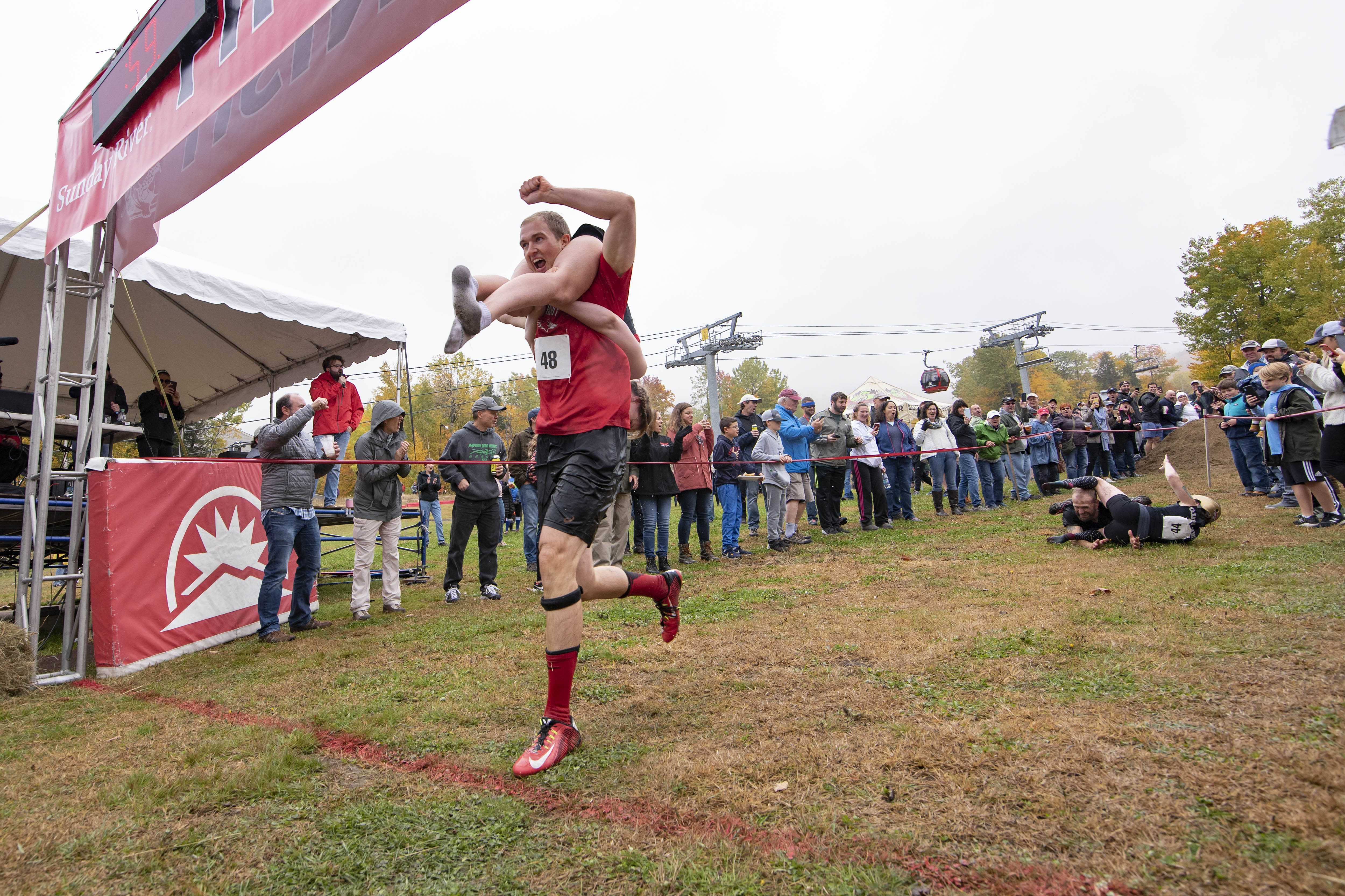Photo of There's a contest in Maine where men carry their spouses across the finish line. The winner gets quite a prize